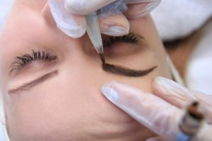 40803588 - cosmetologist applying permanent make up on eyebrows eyebrow tattoo